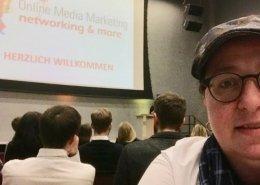 OMM-Tagung Donau Unikrems, Angelika Wohofsky macht ein Selfie im Hintergrund die Powerpoint der Tagung und Besucher