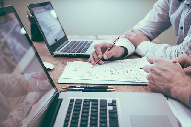 zwei Personen sitzen vor ihren Laptops und besprechen ein Paper, das vor ihnen liegt, Beratung für Content Marketing