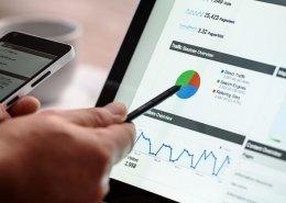 Hand zeigt mit einem Stift auf eine Google Analytics Auswertung