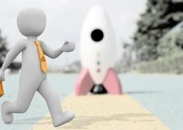 Männchen mit gelber Krawatte und gelbem Aktenkäufer läuft über einen Steg, während im Hintergrund eine Mondrakete steht.