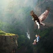 Adler im Flug hält Kind auf einer Schaukel