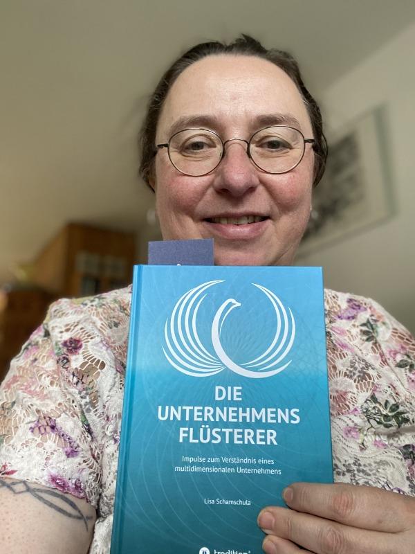 """Angelika Wohofsky hält das Buch """"Die Unternehmensflüsterer"""" in die Kamera."""